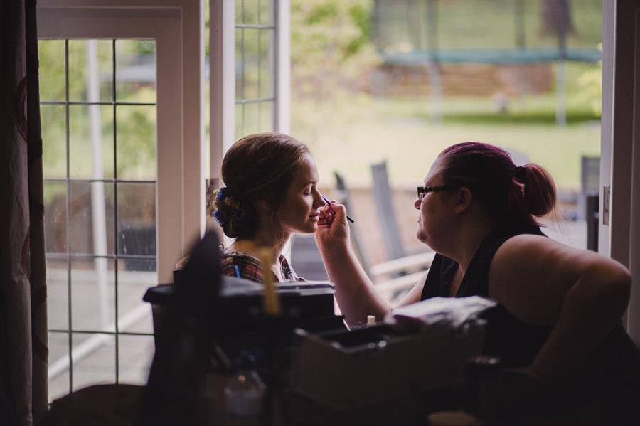 Bride having her makeup done at a window with Ms Moo Make Up
