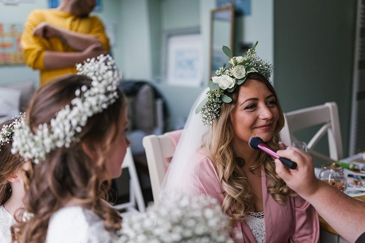 Bride having makeup applied smiling off screen as small girl looks on wearing a flower crown