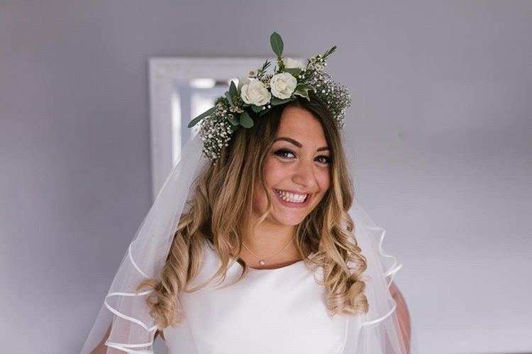 Beaming bride to be wearing muted green flower crown with veil and white dress