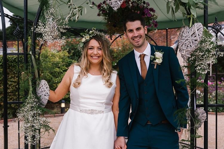 Bride and groom smile at camera under pagoda at The Walled Garden Beeston