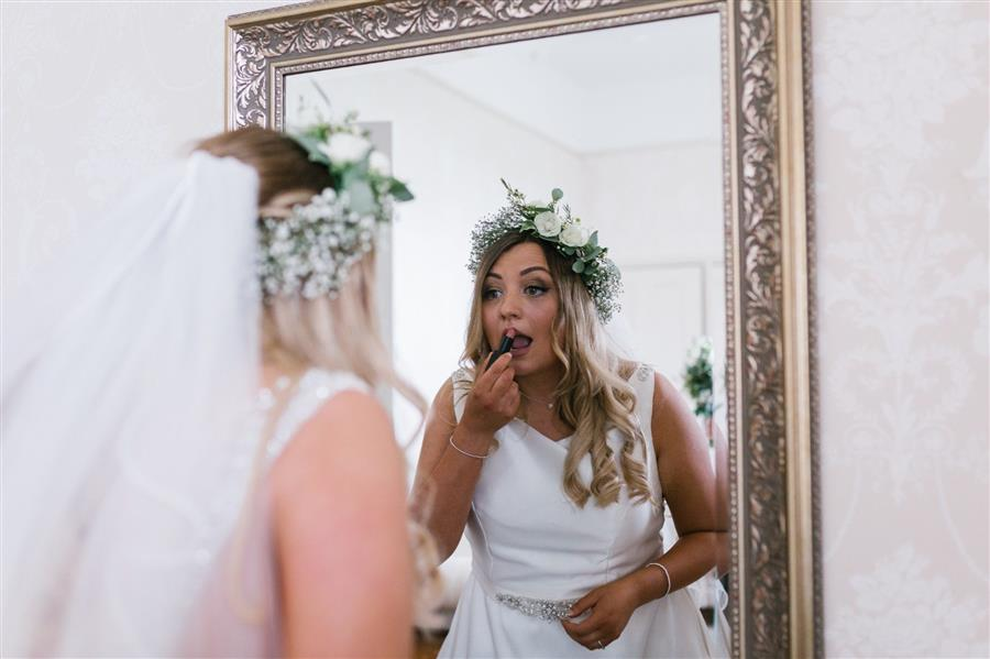 Bride to be applies Illamasqua lipstick in a large mirror wearing a white wedding dress