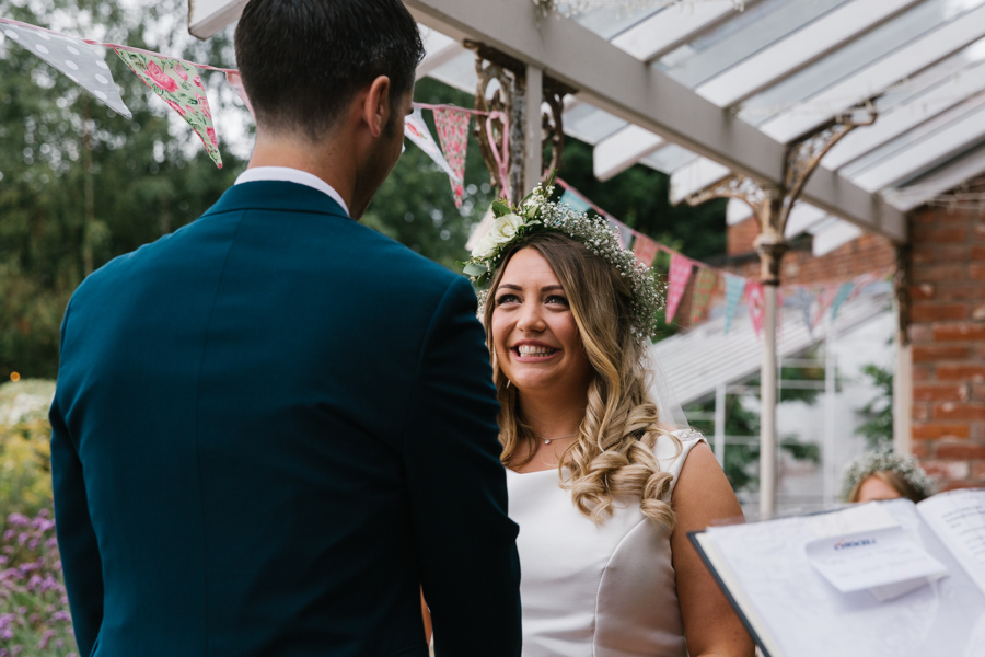 Bride smiles at groom at The Walled Garden Beeston with Emily & Katy Photography