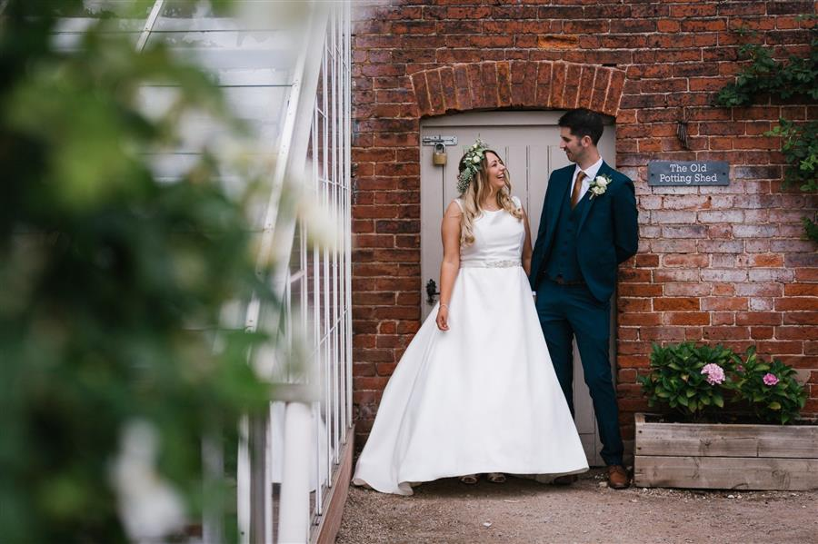 Bride and groom smile at each other in a garden in front of red brick wall by Emily & Katy Photography