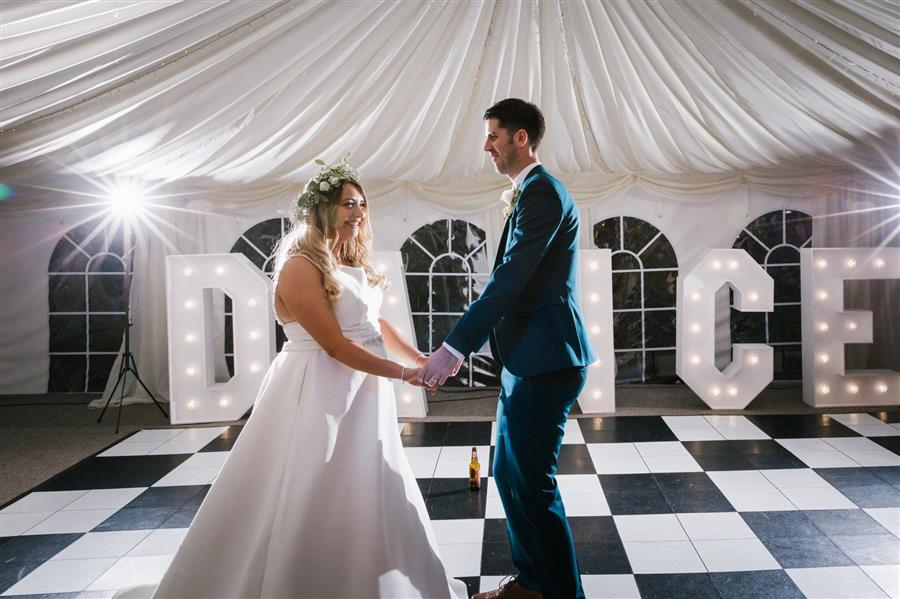 Wedding couple dance on checker board floor in front of light up 'dance' feature