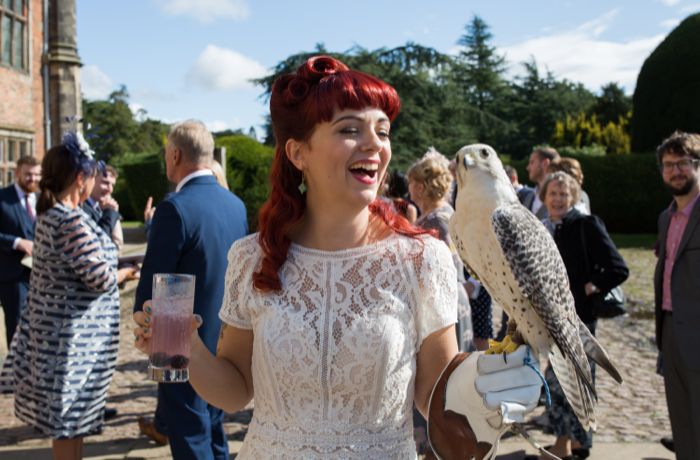Bride with cocktail and owl in sunshine on wedding day