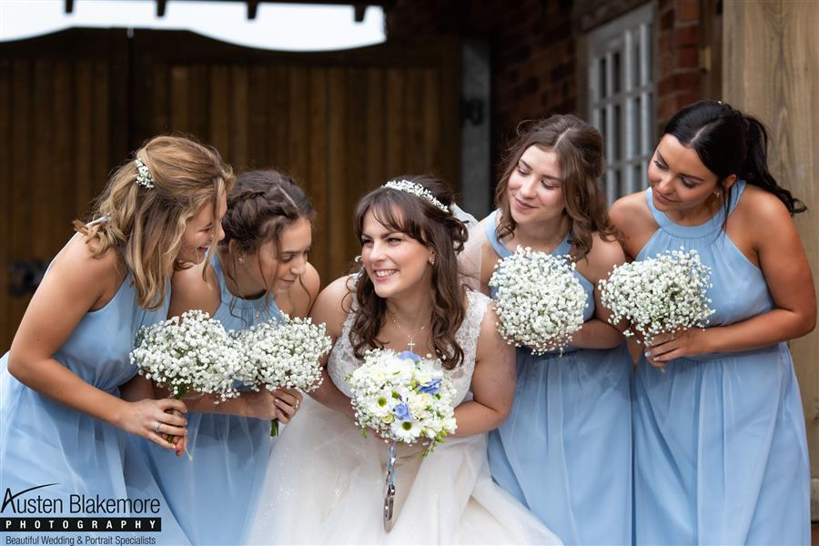 Karah and her bridesmaids all smiling with their bouquets