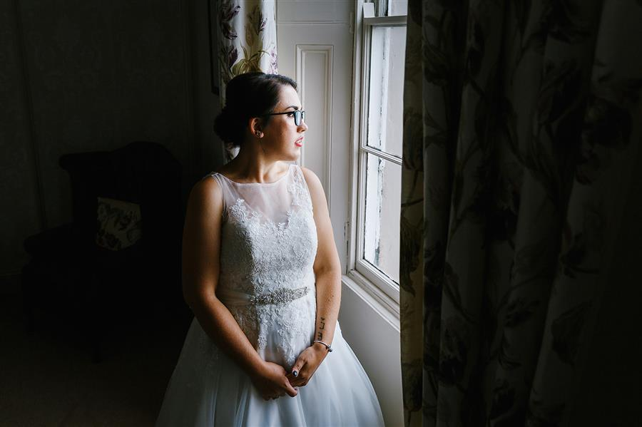 Bride looked out of a window at The Walled Garden Beeston with makeup by Ms Moo