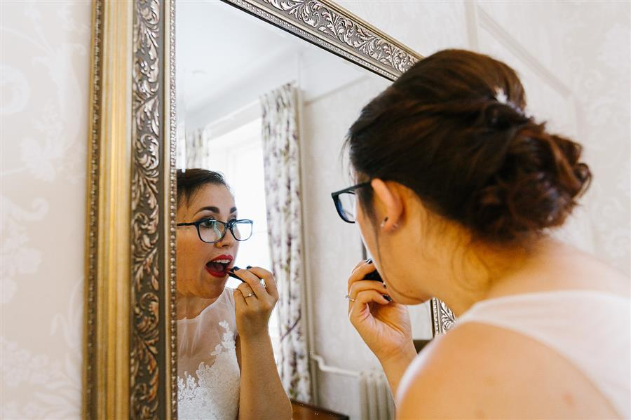Bride applies Illamasqua lipstick in a mirror