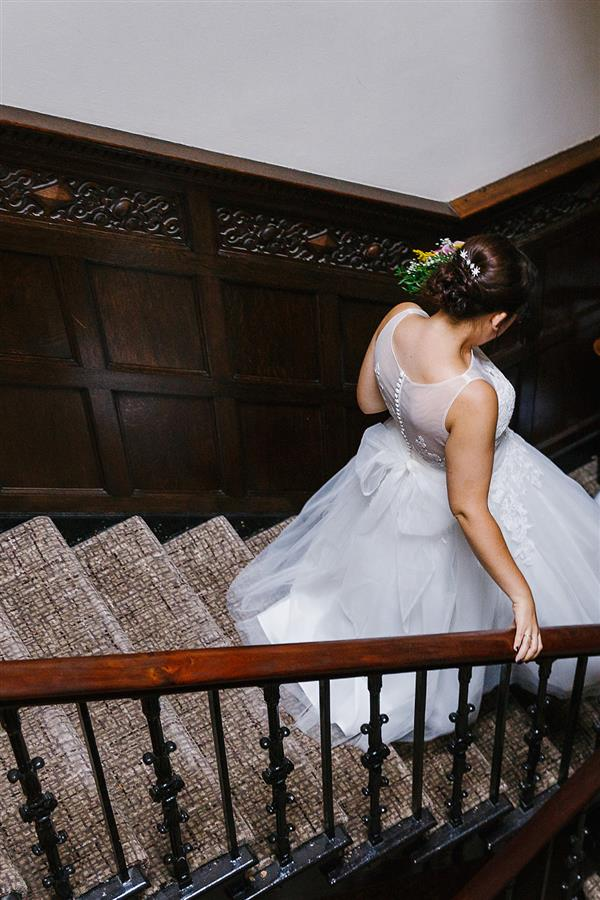 Bride wearing white button up wedding dress going down the stairs