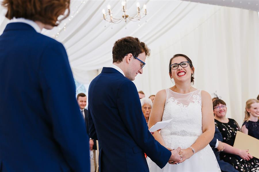 Smiling bride listening to groom make wedding vows by Emily & Katy Photography