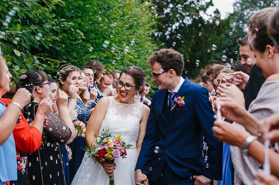 Wedding couple surrounded by bubbles and wedding guests