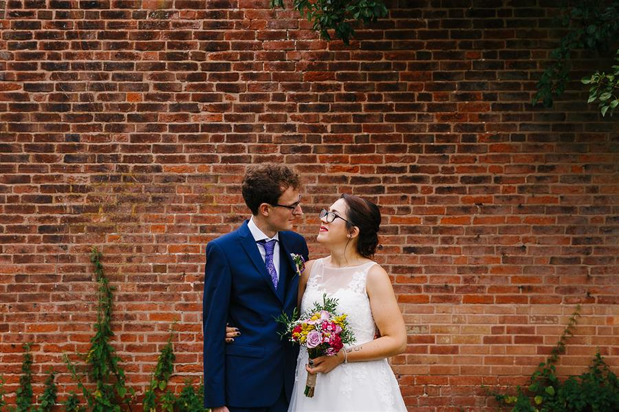 Bride and groom in front of red brick garden wall