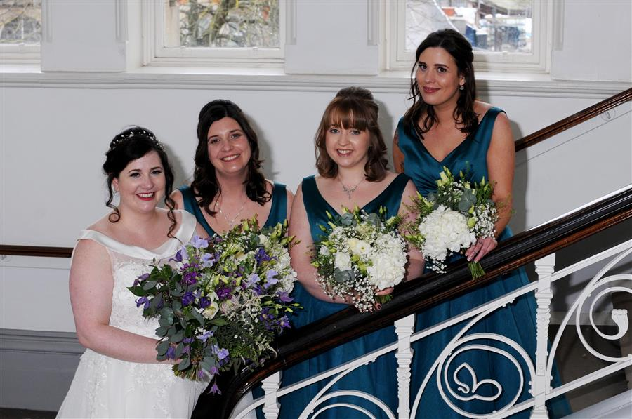 A smiling bride and three bridesmaids in teal with bouquets