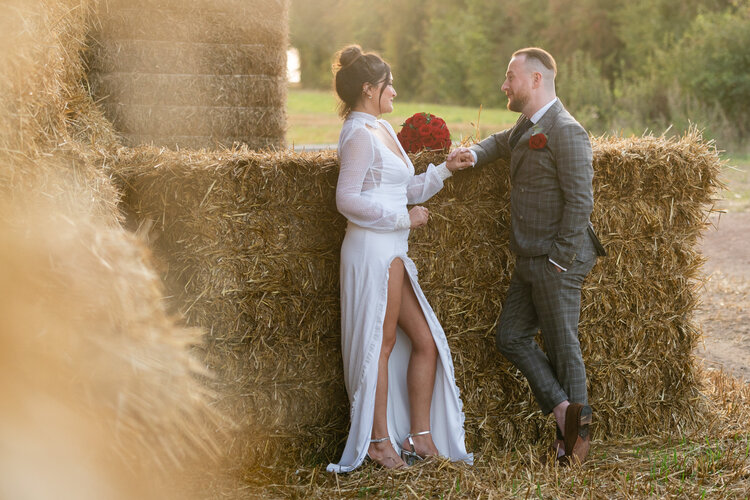 Barn wedding couple next to a hay bale with red rose bouquet and thigh split wedding dress