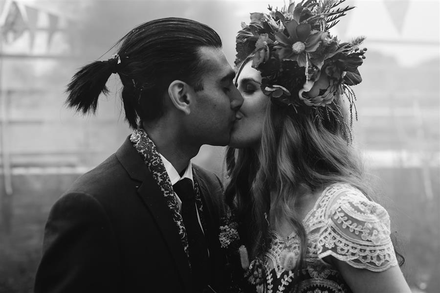 Bride and groom kiss in black and white photo by Camera Hannah