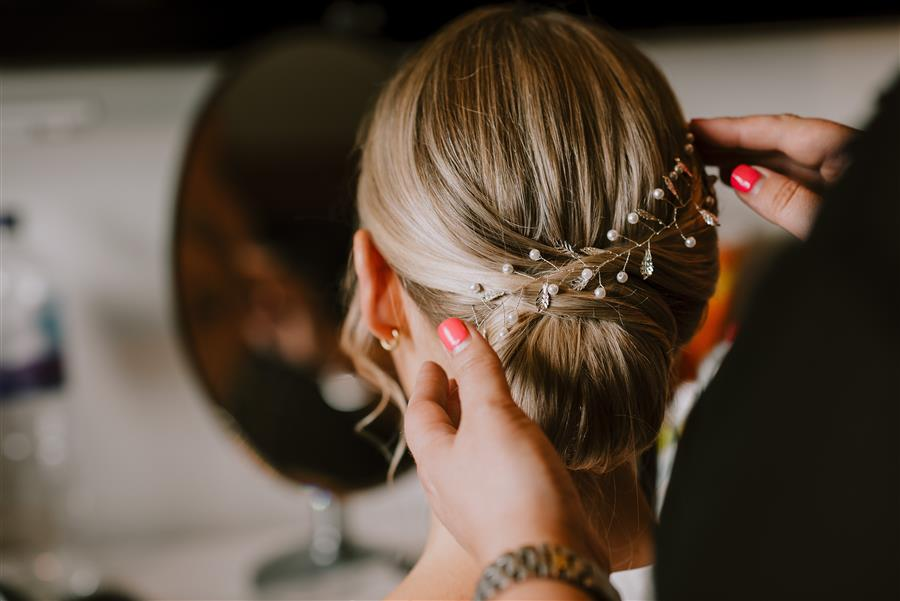 Mon Amie Wedding Hairstylist adjusting hair vine on a blonde wedding client
